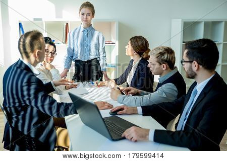 Young businesswoman in ceo position tells something her subordinates