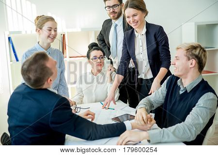 A concept of a business competition in office with two workers arm wrestling