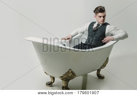 Handsome man or businessman with stylish haircut hair in fashion business wear vest tie shirt and pants relaxing in classic bath white tub on grey background