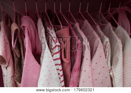 A lot of white children's clothes on hangers. Children's wardrobe with clothes.