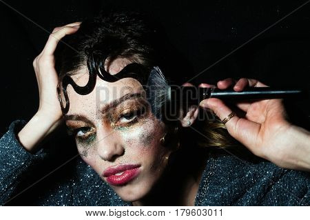 Pretty girl or sexy woman putting holiday glitter makeup sparkling eye shadow rosy lips with make up brush and cute curly lock hair fashion hairstyle on young face on black background