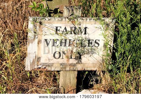 Well worn sign noting only farm vehicles are allowed on the property.