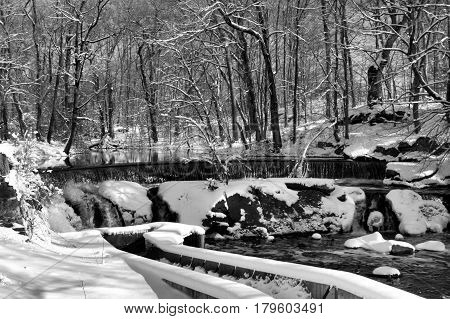 Black and white image of a waterfall and fish ladder on  a sunny day after a snowstorm.