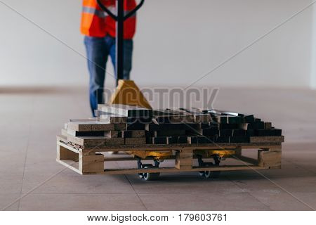 Driving construction material with hand pallet truck color image