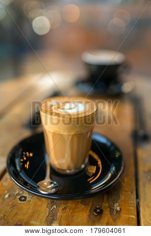 Cup of hot piccolo latte coffee on rustic wooden table close-up. Low depth of field