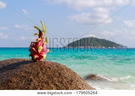 Dragon fruit on sand against turquoise water. Tropical summer vacation concept. Similan Islands Thailand.
