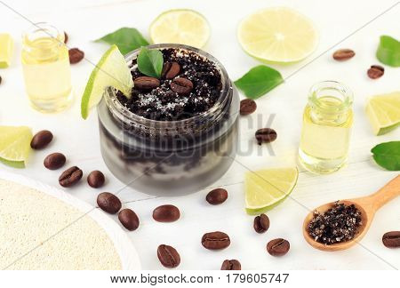 Coffee and sugar grains mix for skin scrub in cosmetic glass jar with slices of fresh green lime fruit, essential oils. Home spa beauty treatment preparation.