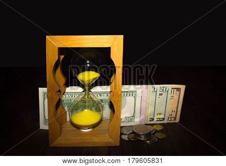 The Glossy Old-style Hourglass Standing With American Dollar Bills