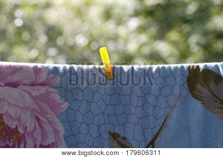 image of one clothespin on blue bedsheet