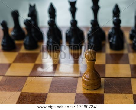 White chess pawn alone on a chessboard. conceptual photo of fighting alone and overcome the life difficulties alone. Self motivation.