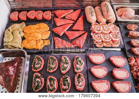 Butcher with various types of meat already filled and ready to be cooked.