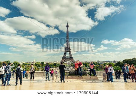 PARIS - SEPTEMBER 20: Tourists walk on a viewing platform in front of the Eiffel Tower on september 20, 2013 in Paris. The Eiffel tower is one of the major tourist attractions of France.
