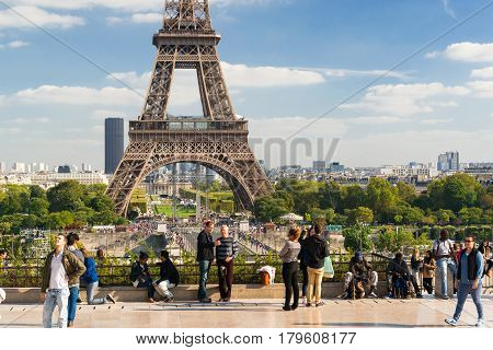PARIS - SEPTEMBER 20: Tourists walk on a viewing platform in front of the Eiffel Tower on september 20 2013 in Paris. The Eiffel tower is one of the major tourist attractions of France.