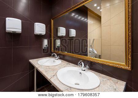 Modern public bathroom with ceramic walls and mirror