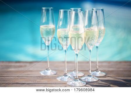 Champagne glasses on wooden background near pool. Summer pool party