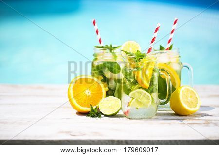 Glasses of citrus lemonade near pool. Summer pool party