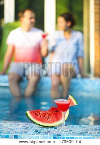 Couple drink watermelon margarita near pool. Cocktail