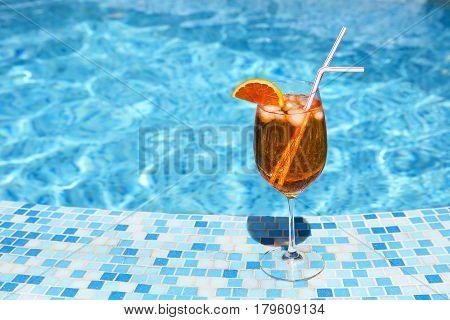 Glass of orange alcohol cocktail near the pool. Spritz
