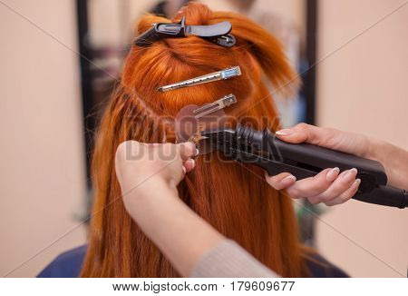 The hairdresser does hair extensions to a young red-haired girl in a beauty salon. Professional hair care.