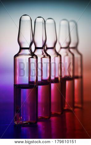 Row of ampulas with medicine on purple background