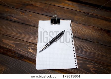 Pen With White Sheet Of Paper In Box With Clerical Clip On Wooden Background. Top View With Copy Spa