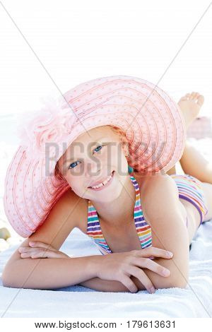 Cute happy child lying down on deckchair of beach resort for summer holidays or travel vacations. Summer vacation idea.