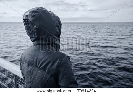 Faceless hooded person looking into distance at horizon over the sea water on cold windy winter day anticipating unpredictable future