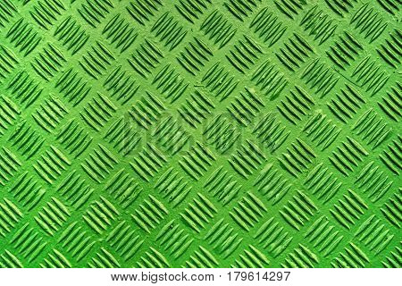 Green metal surface background with repeating diamond pattern old used painted industrial metallic plate texture