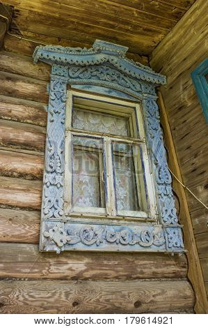 Old window of a village house with carved platbands