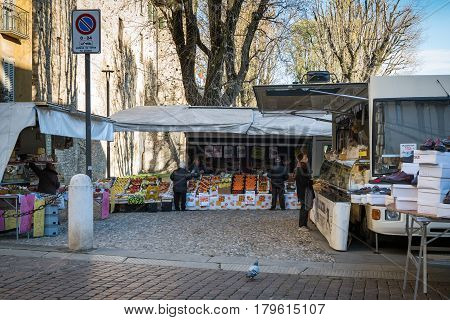 BERGAMO, ITALY - DECEMBER 2016: People are buying fruits and other goods at small market place of Bergamo town.