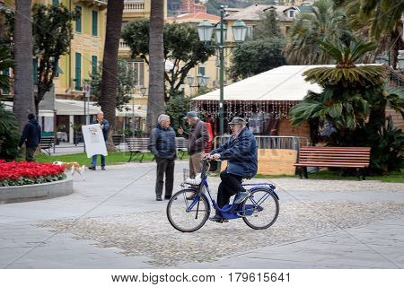 SANTA MARGHERITA LIGURE - DECEMBER 2016: Old man is driving by bicycle on street of Santa Margherita town, Liguria, Italy