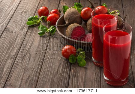 Healthy eating dieting and vegetarian concept - glass juices of beet-tomato juice with vegetables on dark wooden background . Detox and healthy diet. Copy space.