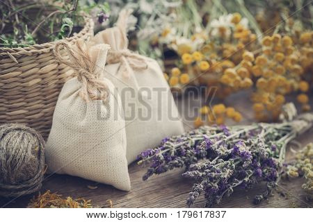 Sachets filled with dried medicinal herbs and bunches of healing herbs on wooden board. Herbal medicine. Retro toned.