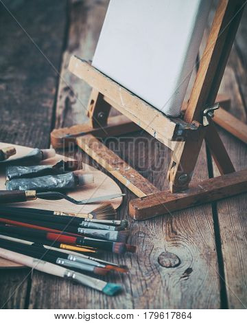Artistic Equipment: White Artist Canvas On Easel, Palette And Paint Brushes In A Artist Studio. Retr