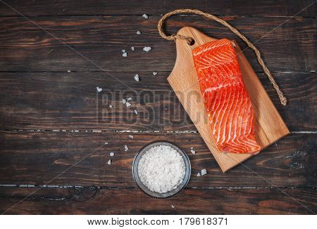 Salmon filet with salt on a wooden carving board. Top view