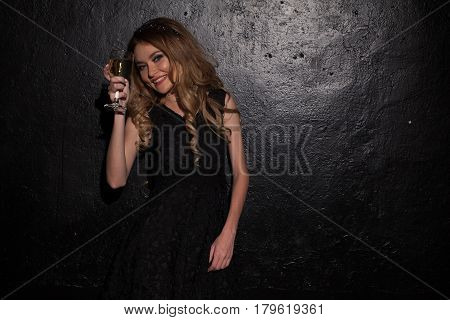 a girl in a black evening gown with a glass of wine