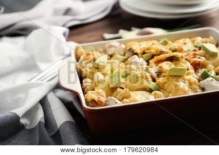 Roasted chicken with cheese in casserole dish on kitchen table