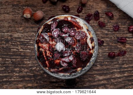 Cake with berries in chocolate on a white napkin on an old wooden table rustic style