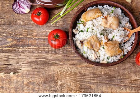 Bowl with tasty chicken and rice on wooden table