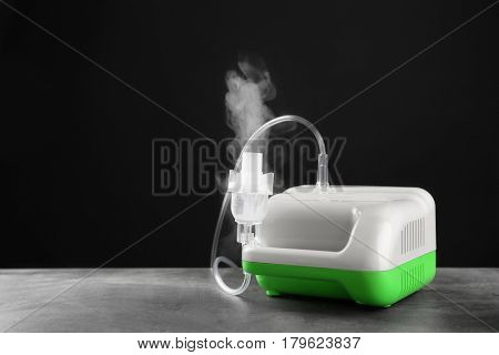 Compressor nebulizer on table against black background