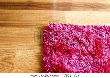 Pink Purple Rug On Wooden Floor Cropped Detail