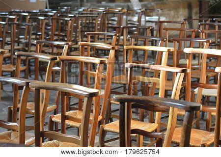 Row of wooden chairs inside a church in France.