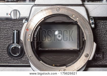 Old film camera front panel with lens mount, mirror and focusing screen. Close-up macro photo of retro black and silver SLR