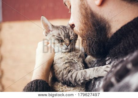 Close-up of handsome young man who is standing on a balcony with his cat. Home pets. Beard man in icelandic sweater is holding and hugging his cute curious Devon Rex cat with closed eyes.