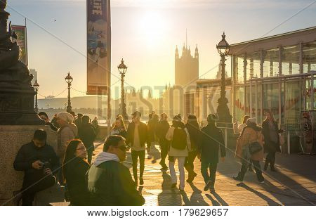 London, UK - November 30, 2016: Houses of Parliament and people walking on the River Thames embankment at sunset