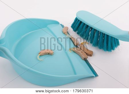 Old and used hearing aids small plastic broom and shovel - Electronic waste