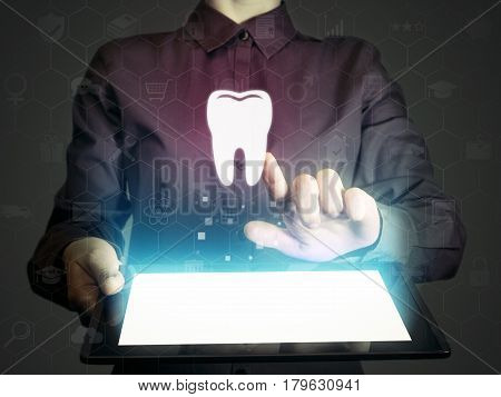Image of a girl with tablet pc in her hands and tooth icon. Search for dentists dental services consultations.