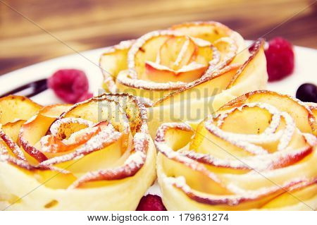 apple muffins with raspberry in a white plate on a wooden background