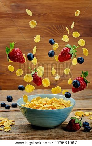 Healthy breakfast with flying corn flakes strawberries and blueberries.