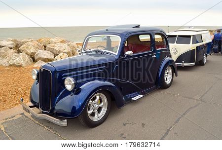 FELIXSTOWE, SUFFOLK, ENGLAND - AUGUST 27, 2016: Classic Blue Ford Motor Car  with trailer shaped like a VW Camper Van  parked on seafront promenade.